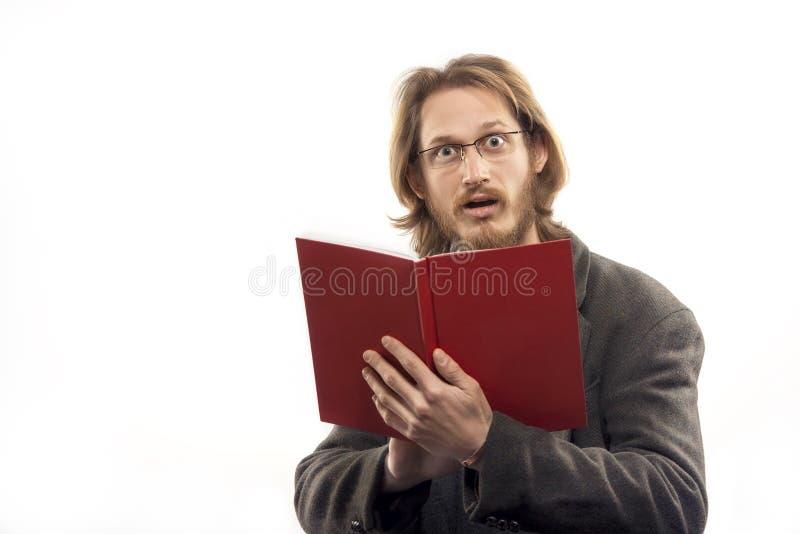 Homem surpreendido com livro vermelho fotografia de stock