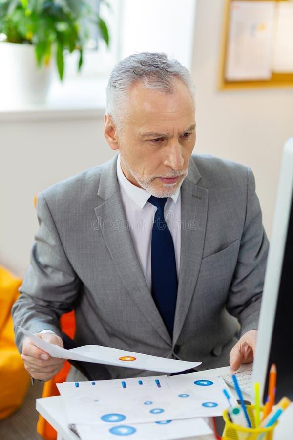 Homem surpreendido com o restolho cinzento que compara dados na tela fotografia de stock
