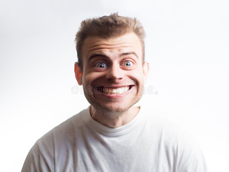 Homem surpreendido em uma camisa branca de t em um fundo branco com uma cara dos desenhos animados surpreendido por discontos, ex foto de stock royalty free