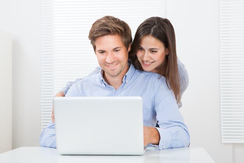 Homem surpreendido que olha a mulher ao usar o portátil fotos de stock