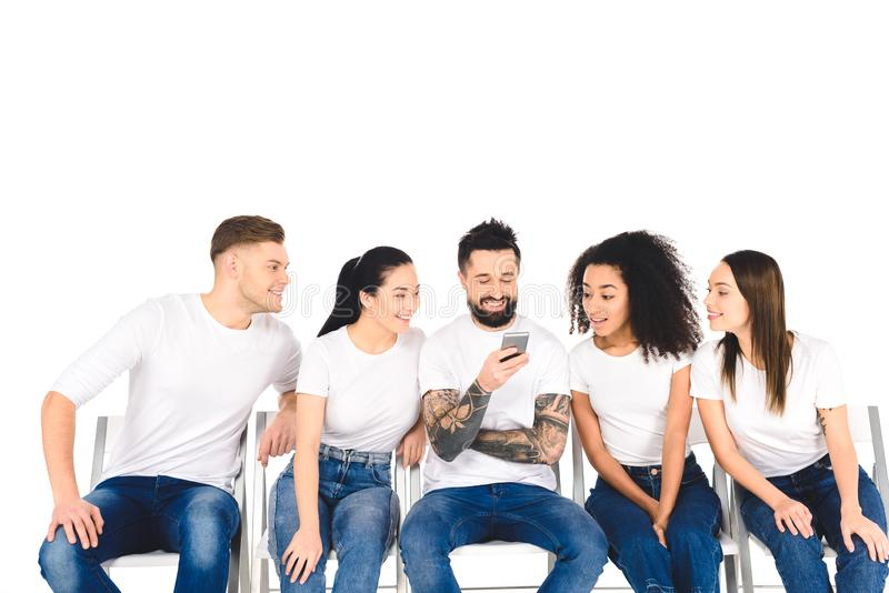 homem tattooed de sorriso que usa o smartphone quando jovens curiosos multi-étnicos que olham a tela isolada fotografia de stock royalty free