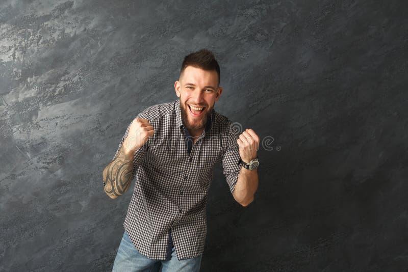 Homem tattooed entusiasmado muito contente ao sucesso fotografia de stock royalty free