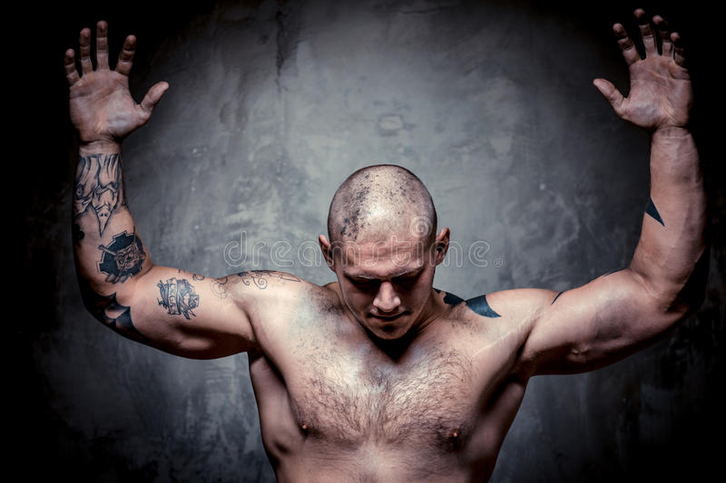 Homem tattooed muscular com as mãos levantadas acima foto de stock royalty free