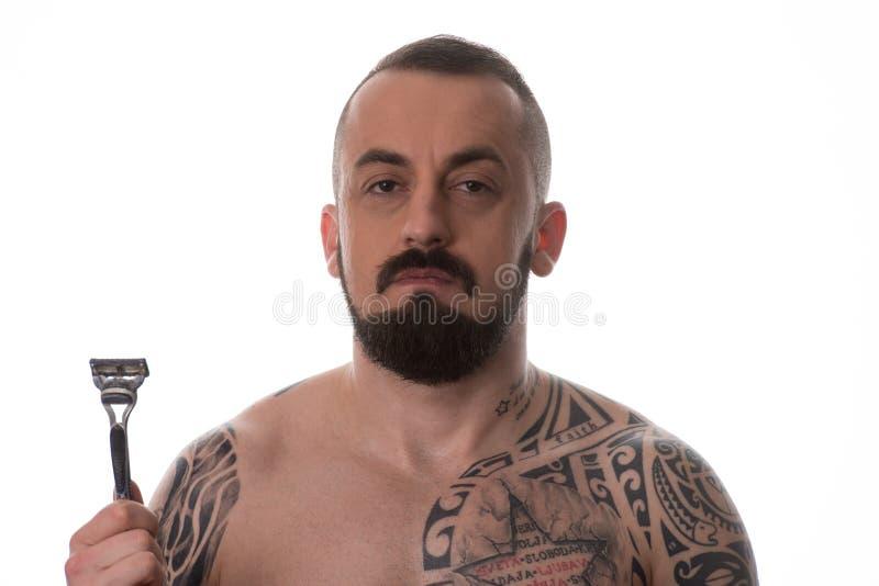 Homem Tattooed que denomina a barba que guarda a lâmina descartável imagens de stock