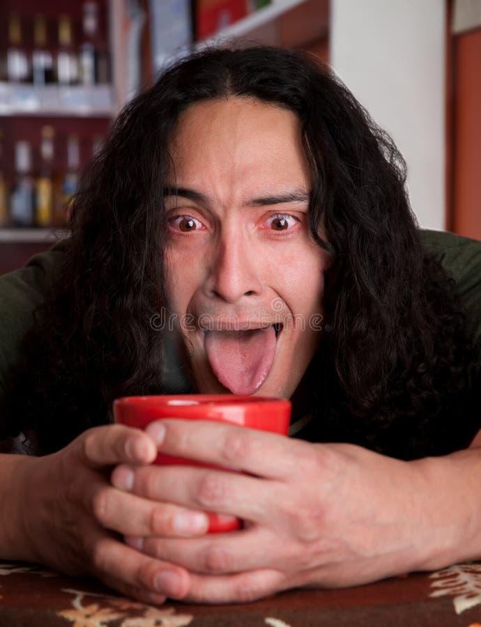 Homem Tired do Latino que embala o copo de café vermelho imagens de stock