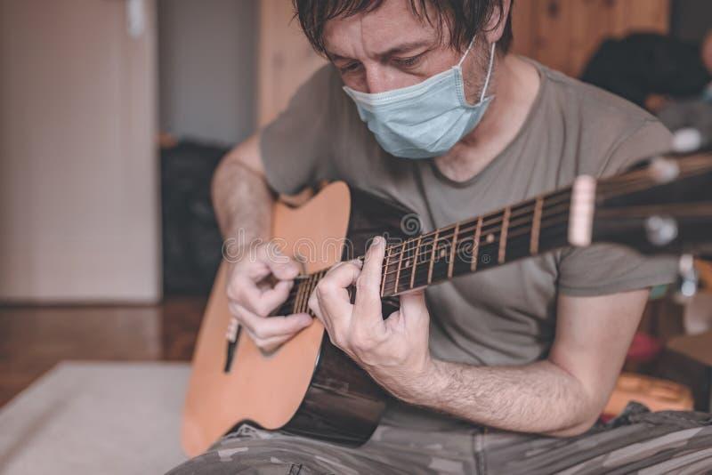 Homem tocando guitarra acústica em quarentena caseira autoisolamento imagem de stock