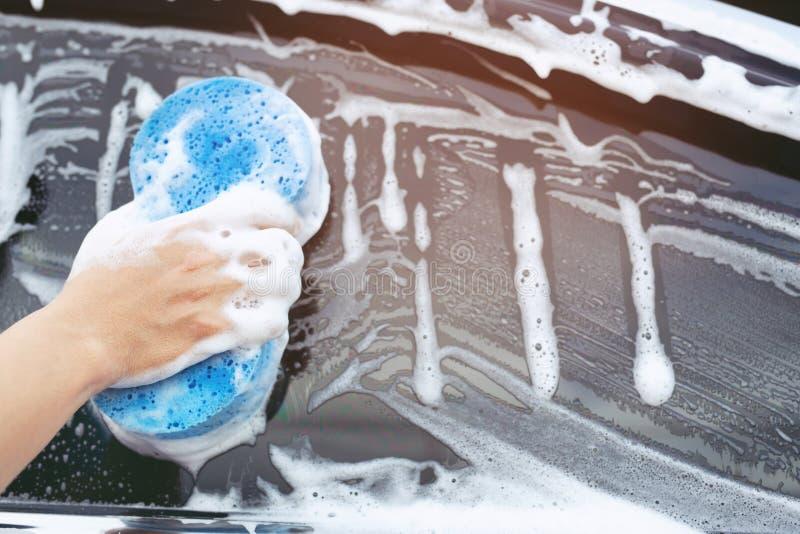 Homem trabalhador segurando uma esponja azul de mão e uma janela de limpeza de espuma de bolhas para lavar o carro Conceito limpe foto de stock