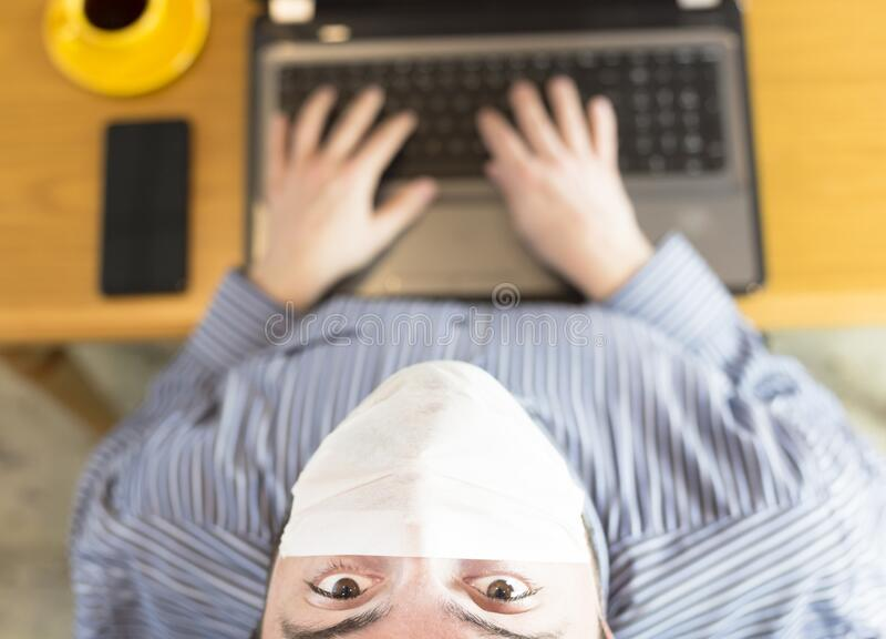Homem trabalhando em casa no laptop Covid-19 imagens de stock