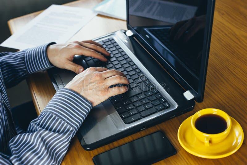 Homem trabalhando em um laptop em uma mesa de madeira rústica, mãos fechadas fotografia de stock