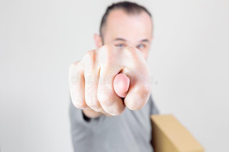 Homem triguenho caucasiano com a cara obscura que guarda uma caixa marrom, mostrando o figo no fundo branco foto de stock
