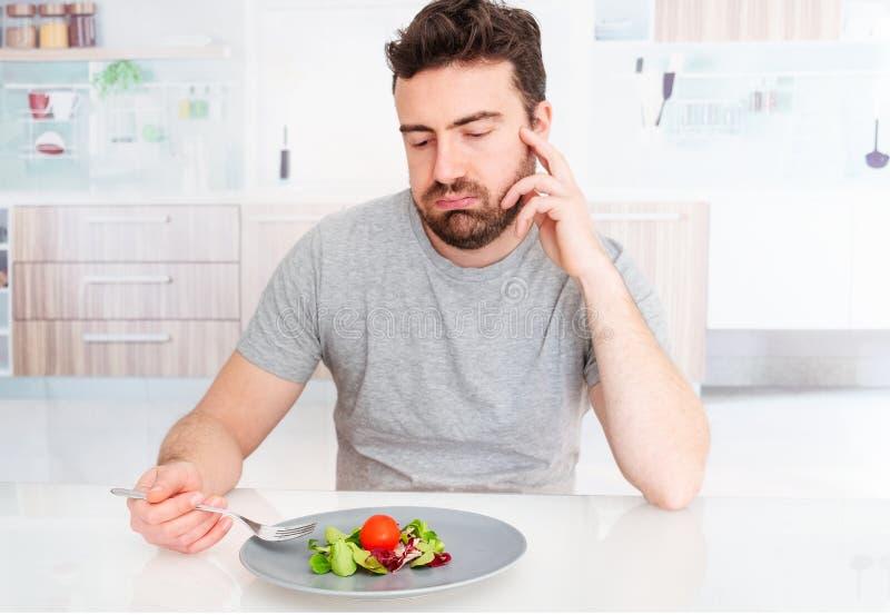 Homem triste for?ado a comer a salada para a perda de peso imagem de stock royalty free