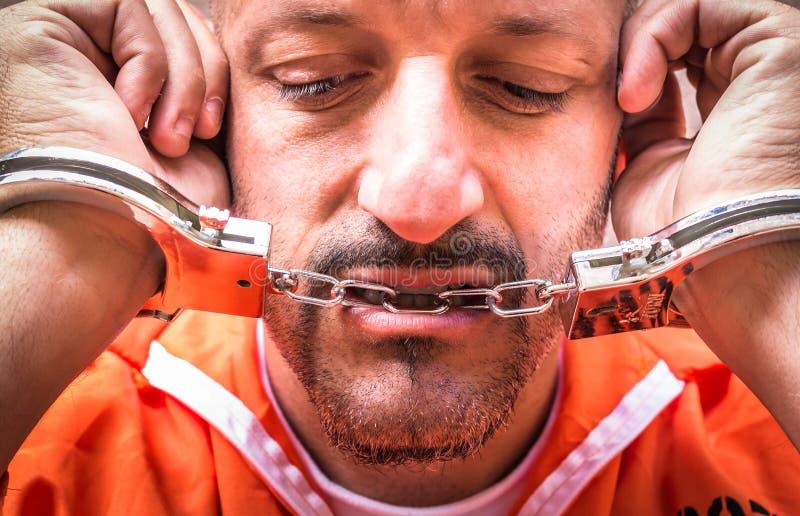 Homem triste com as algemas na prisão fotografia de stock royalty free