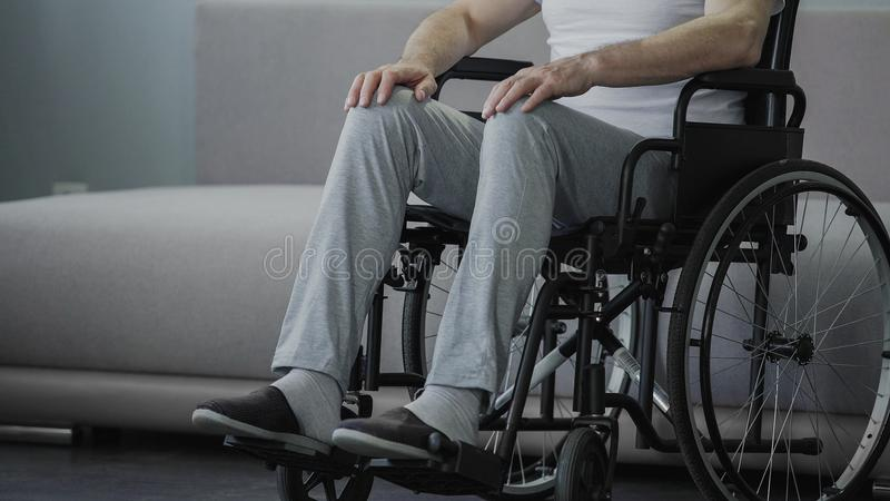 Homem triste com as inabilidades que sentam-se na cadeira de rodas sozinha, solidão de sofrimento fotografia de stock