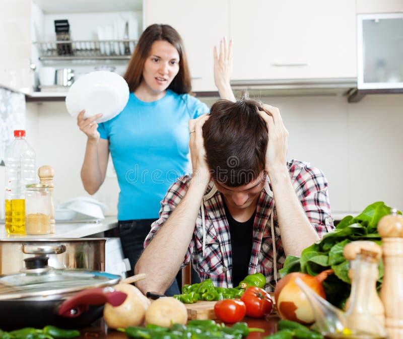 Homem triste com a esposa irritada na cozinha foto de stock