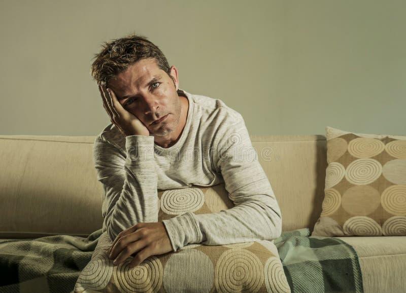 Homem triste e desesperado novo em casa que senta-se no sofá do sofá que mantém a depressão e o esforço de sofrimento do descanso fotos de stock royalty free