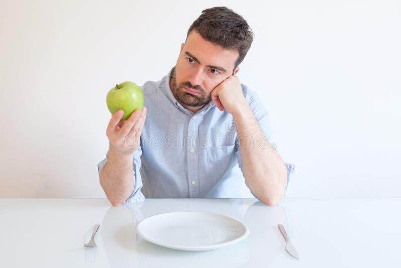 Homem triste e frustrante na dieta que come somente o fruto para a refeição fotografia de stock