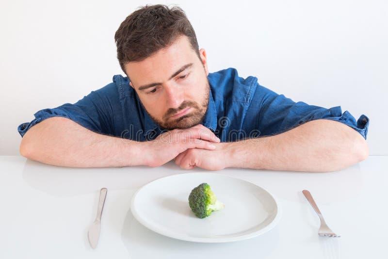 Homem triste e frustrante na dieta que tem somente vegetais para a refeição fotografia de stock