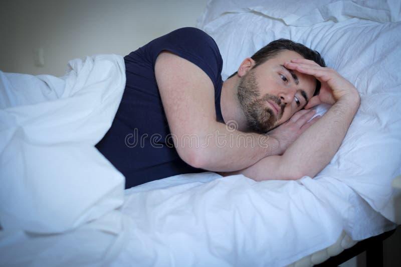 Homem triste e virado que tenta dormir na cama imagem de stock