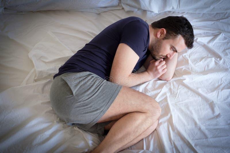 Homem triste e virado que tenta dormir na cama fotografia de stock royalty free