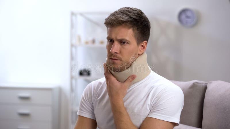 Homem triste no colar cervical da espuma que toca no pescoço, virada de sentimento após o traumatismo foto de stock