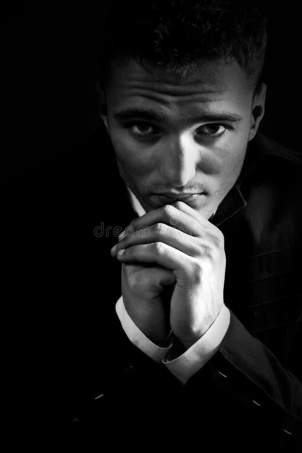 Homem triste no praying escuro ao deus