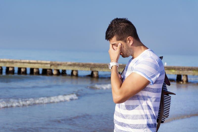 Homem triste novo que está apenas na praia fotos de stock