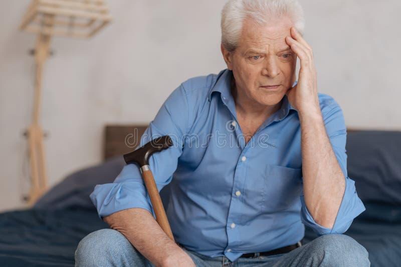 Homem triste pensativo que está sendo envolvido em seus pensamentos fotografia de stock