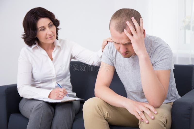 Homem triste que fala sobre seus problemas com doutor fotos de stock royalty free