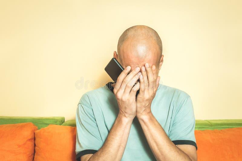 Homem triste que guardam seu telefone celular em suas mãos e grito porque sua amiga quebra acima com ele sobre a mensagem de text imagem de stock royalty free
