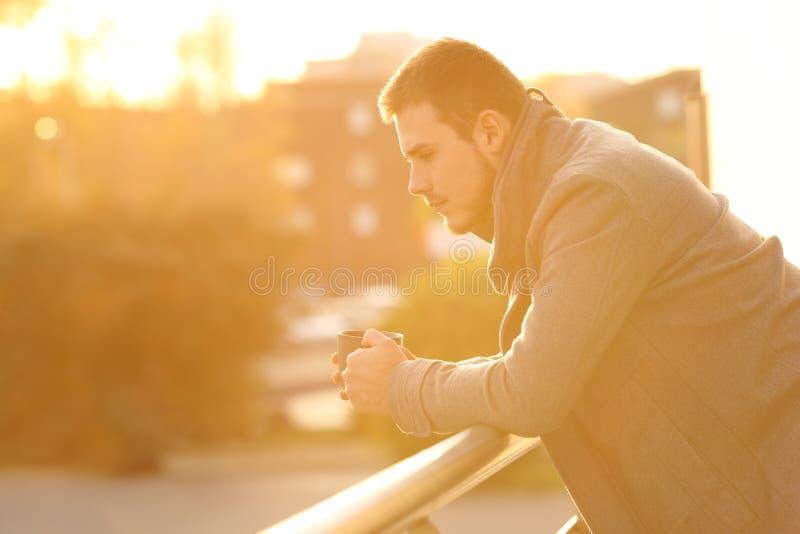 Homem triste que olha para baixo em um balcão no inverno imagens de stock