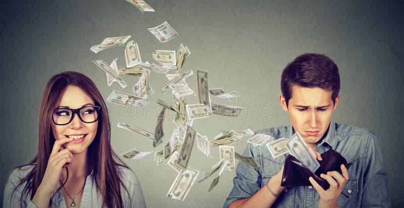 Homem triste que olha sua carteira com as cédulas do dólar do dinheiro que voam afastado para flertar a jovem mulher bonito fotografia de stock