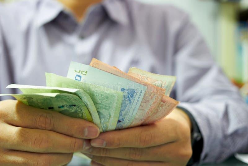 Homem uniforme está contando Nota de dinheiro para o conceito de problema de crise econômica fotografia de stock
