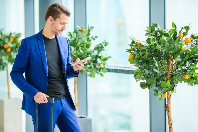 Homem urbano com o telefone celular no aeroporto Revestimento vestindo do terno do menino novo ocasional Homem caucasiano com o t foto de stock royalty free