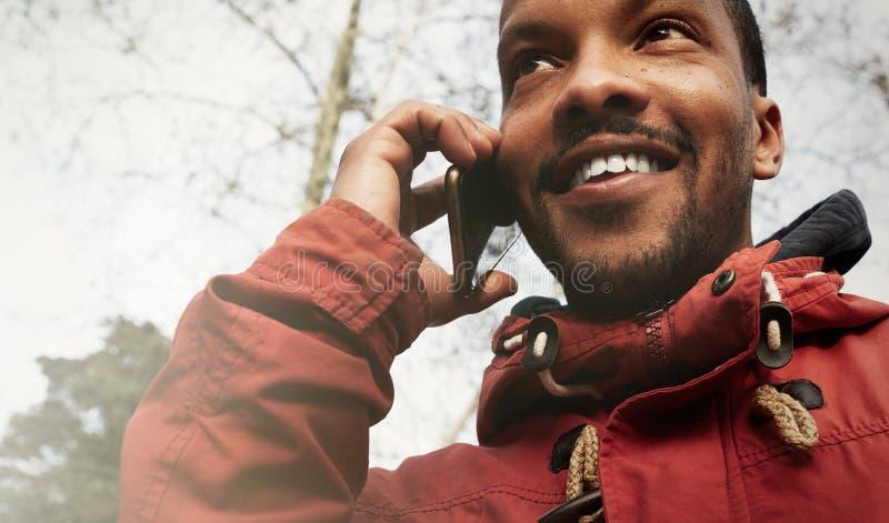 Homem urbano de sorriso feliz novo do moderno da opinião do close up que veste a roupa informal e que usa o telefone esperto Terr imagem de stock royalty free