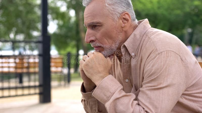 Homem velho comprimido que grita no banco de parque apenas, problemas da aposentadoria, dor da alma fotografia de stock royalty free