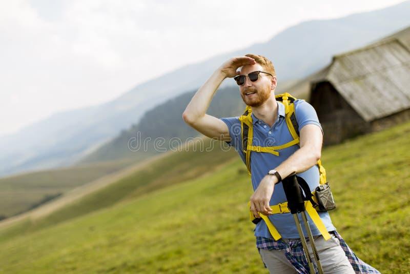 Homem vermelho novo considerável do cabelo com os óculos de sol que caminham na montanha fotografia de stock