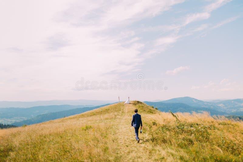 Homem vestido à moda, guardando uma garrafa do vinho que fecha-se ao monte com a menina solitária no vestido branco sob céu nebul fotografia de stock