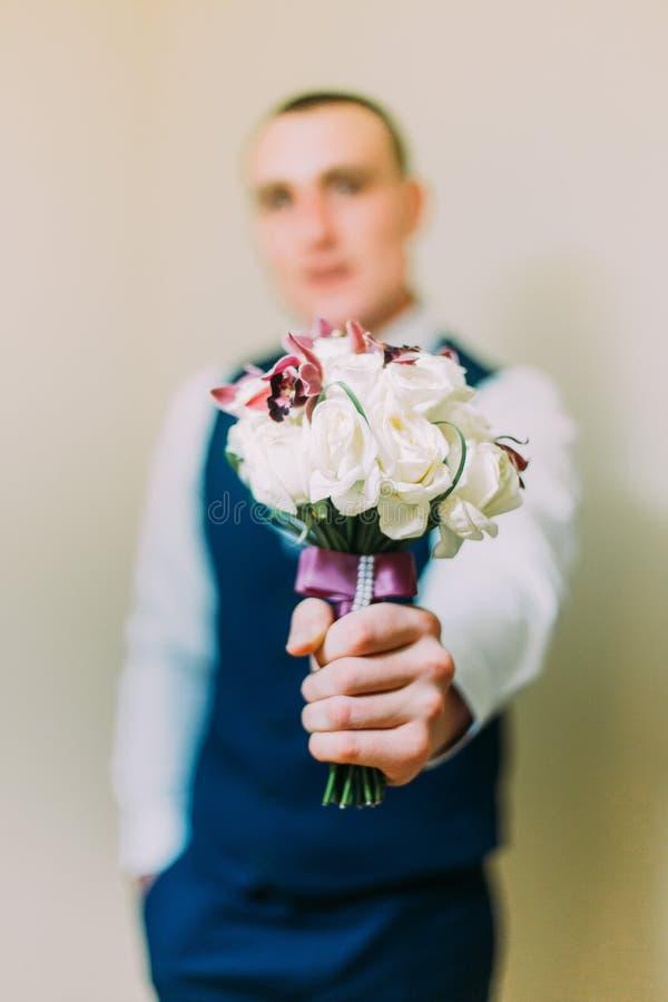 Homem vestido à moda que mantém o ramalhete elegante interno Foco em flores com imagem borrada da pessoa foto de stock royalty free