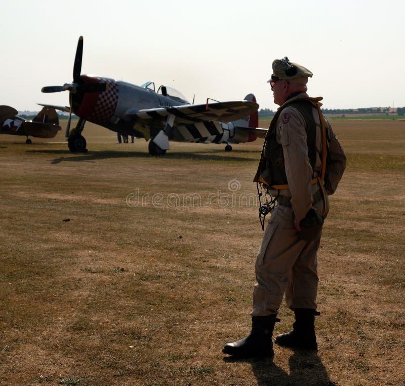 Homem vestido como o piloto americano da segunda guerra mundial com o lutador do raio P47 da república imagens de stock royalty free