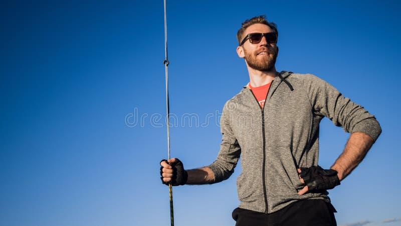 Homem vestido no vestu?rio desportivo e nos ?culos de sol em um iate Retrato farpado adulto feliz do close-up do 'yachtsman' Mari foto de stock