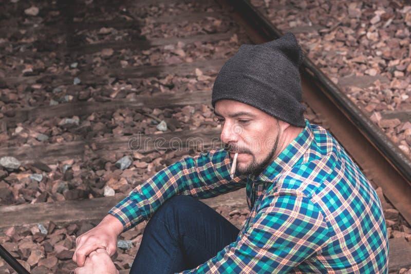 Homem vestido ocasionalmente fumando um cigarro foto de stock