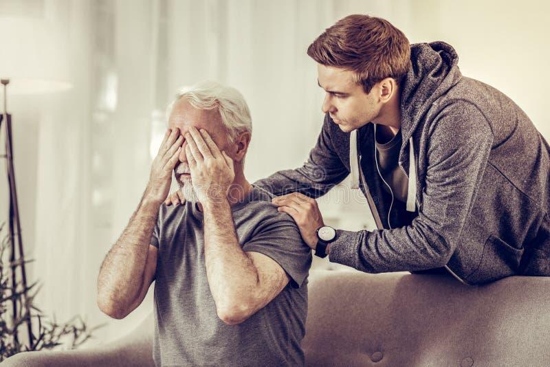 Homem virado atraente novo que abraça calmingly o avô cinzento-de cabelo doloroso doente fotos de stock royalty free