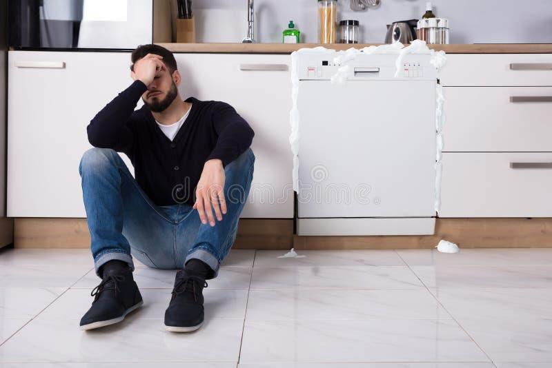 Homem virado que senta-se ao lado da máquina de lavar louça imagem de stock