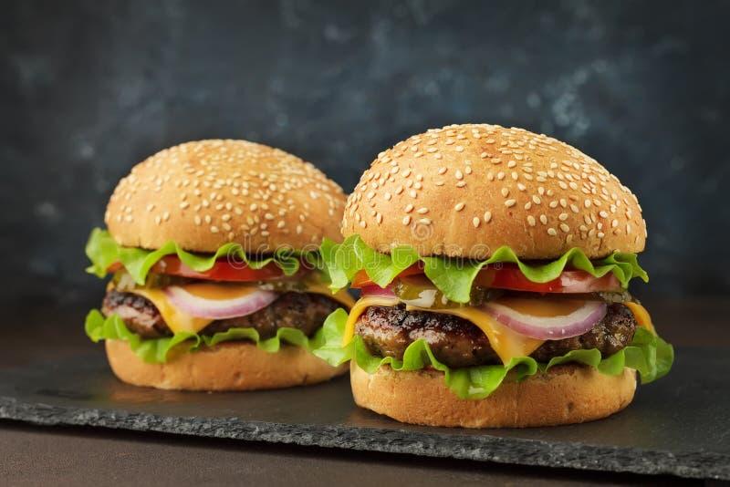 Homemad快餐:两个汉堡用牛肉,切达乳酪,莴苣,葱在板岩板的ang蕃茄 库存图片