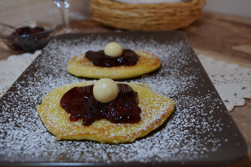 Homemade American Pancakes With Cherry Jam. And Icing Sugar On The Brown Plate stock photo
