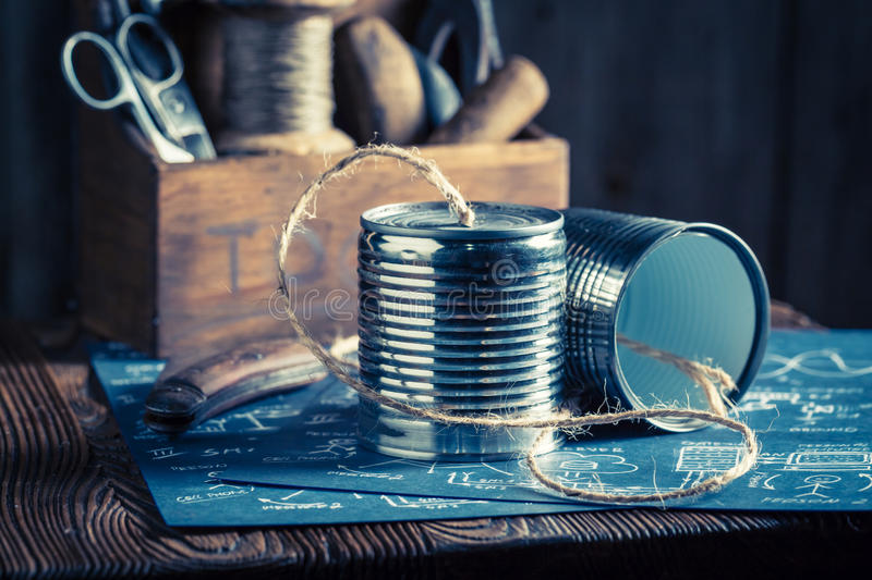 Homemade analog telephone made of cans and string. On old wooden table stock photos