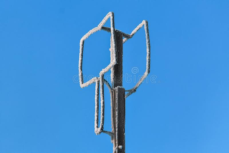 A homemade antenna in the form of a rectangular screen of aluminum wire is tied to a wooden pole against a blue sky on a winter. Frosty day..The concept of an stock photo