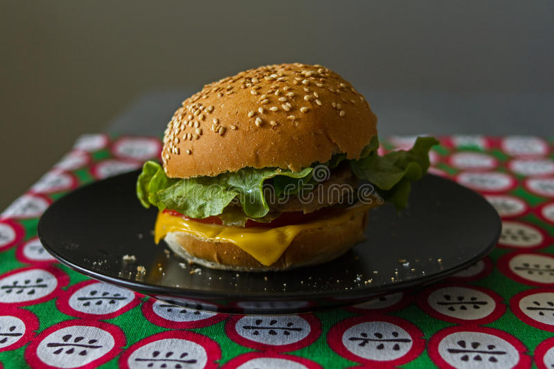 Homemade appetizing cheeseburger with melted cheese in a toasted bun with sesame on a red tablecloth on a gray background. stock photography