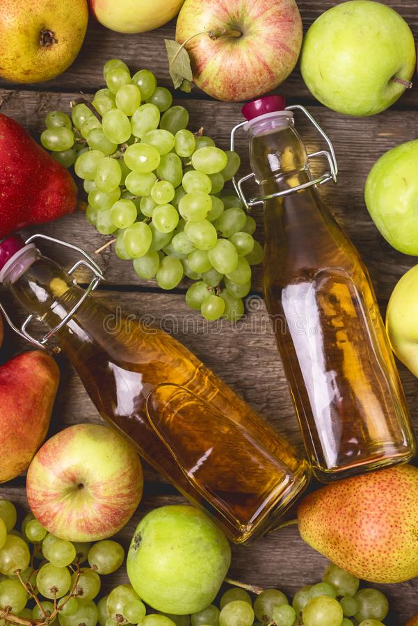 Homemade Apple Cider Vinegar Flatlay of Fresh Ripe Apples Pears and Green Grapes Two Bottles of Apple Juice or Tasty Cider Top. View Wooden Background royalty free stock image