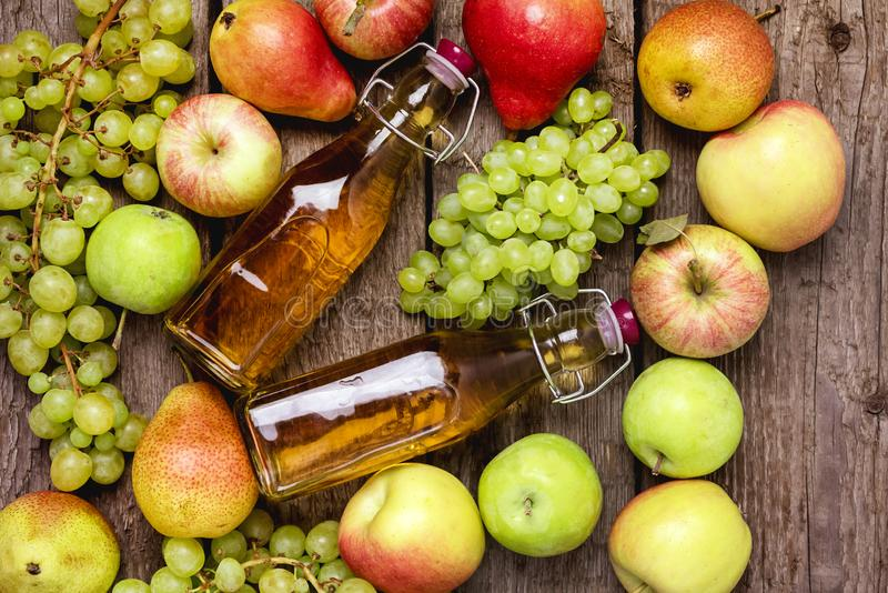 Homemade Apple Cider Vinegar Flatlay of Fresh Ripe Apples Pears and Green Grapes Two Bottles of Apple Juice or Tasty Cider Top royalty free stock image
